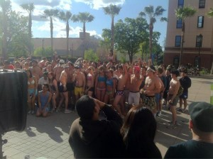 75 students gathered around in underwear with 8 palm trees and a blue sky behind them.