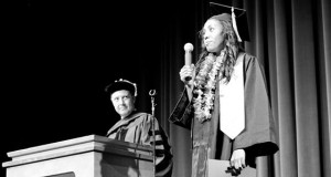 A man at a podium on the left looks at a young woman wearing her graduation cap and gown, holding a microphone. Photo by Christina Olivas