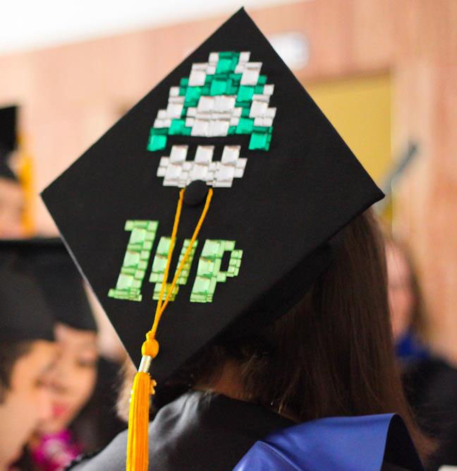 Close-up photo of a graduation cap with yellow tassel that has a green-and-white toadstool with the phrase 1up from the Mario video games. Photo by Christina Olivas