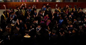 Graduates standing up and looking excited in Morris Dailey Auditorium (Dillon Adams photo).