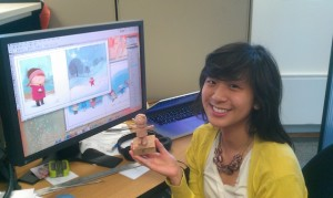 Female student intern sitting in front of her desk modeling her figurine and card creation