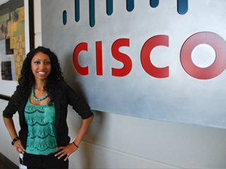 Female Cisco student dressed in a black jacket and turquiose shirt is standing with arms opened in front of a giant Cisco sign