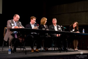 A discussion panel of industry professionals are sitting in chairs at a table on a stage