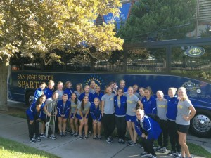 Group of SJSU female soccer players posing next to a bus