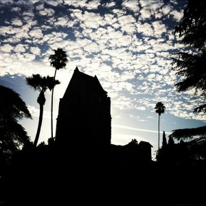 Silhouette of Tower Hall and palm trees with cloudy, blue sky