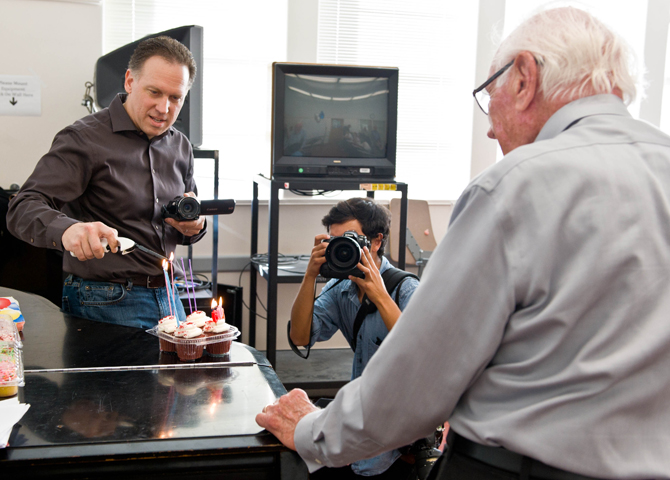 Man lights candles on cupcake while another takes photos of 90-year-old man