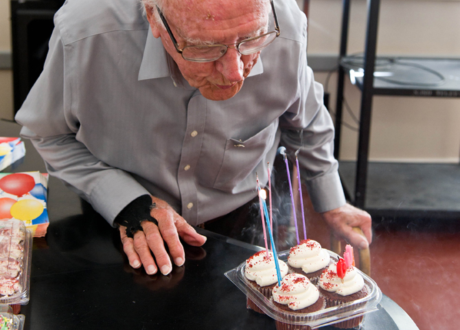 90-year-old man blows candles from cupcakes