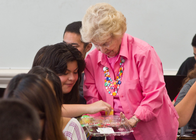 Students takes a cupcake from a woman