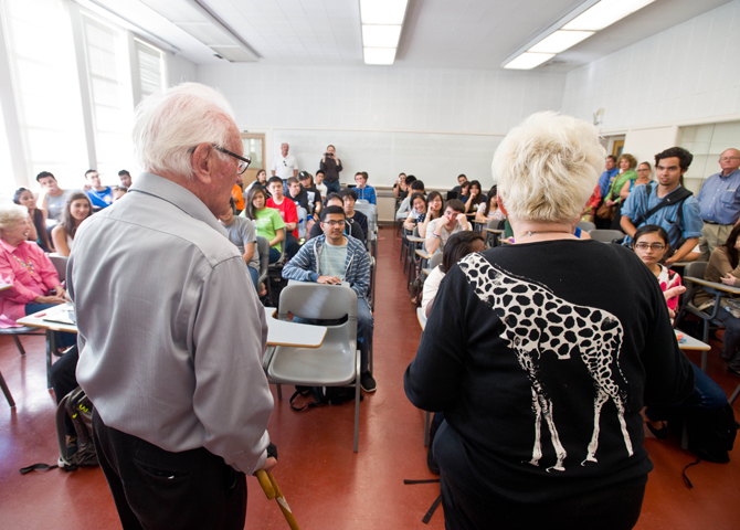 The backs of 90-year-old man and woman looking at the classroom full of students and guests