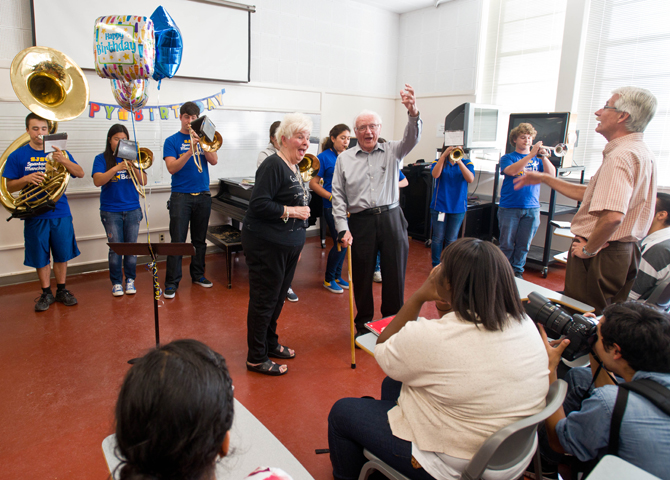 Woman and 90-year-old man sing to class with band director conducting and the band playing music.
