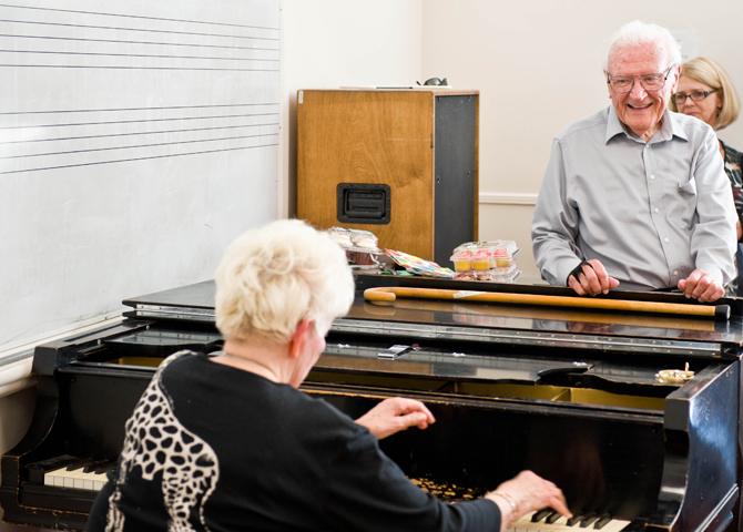 Woman plays on piano while 90-year-old man smiles, standing up.