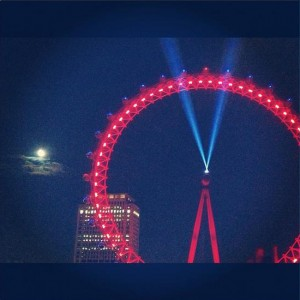 London Eye ferris wheel at night with red lights and blue beacons of light