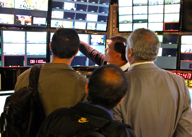A few men looking at TV station control room with many monitors. Photo by Jessica Olthof.