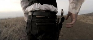 Backside view of cowboy grabbing gun
