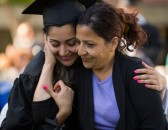 woman and daughter in graduation outfit hugging