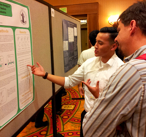 SJSU student shows visitor a poster for his project.