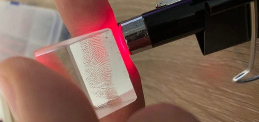 Student holding a cube with a laser shooting through it.