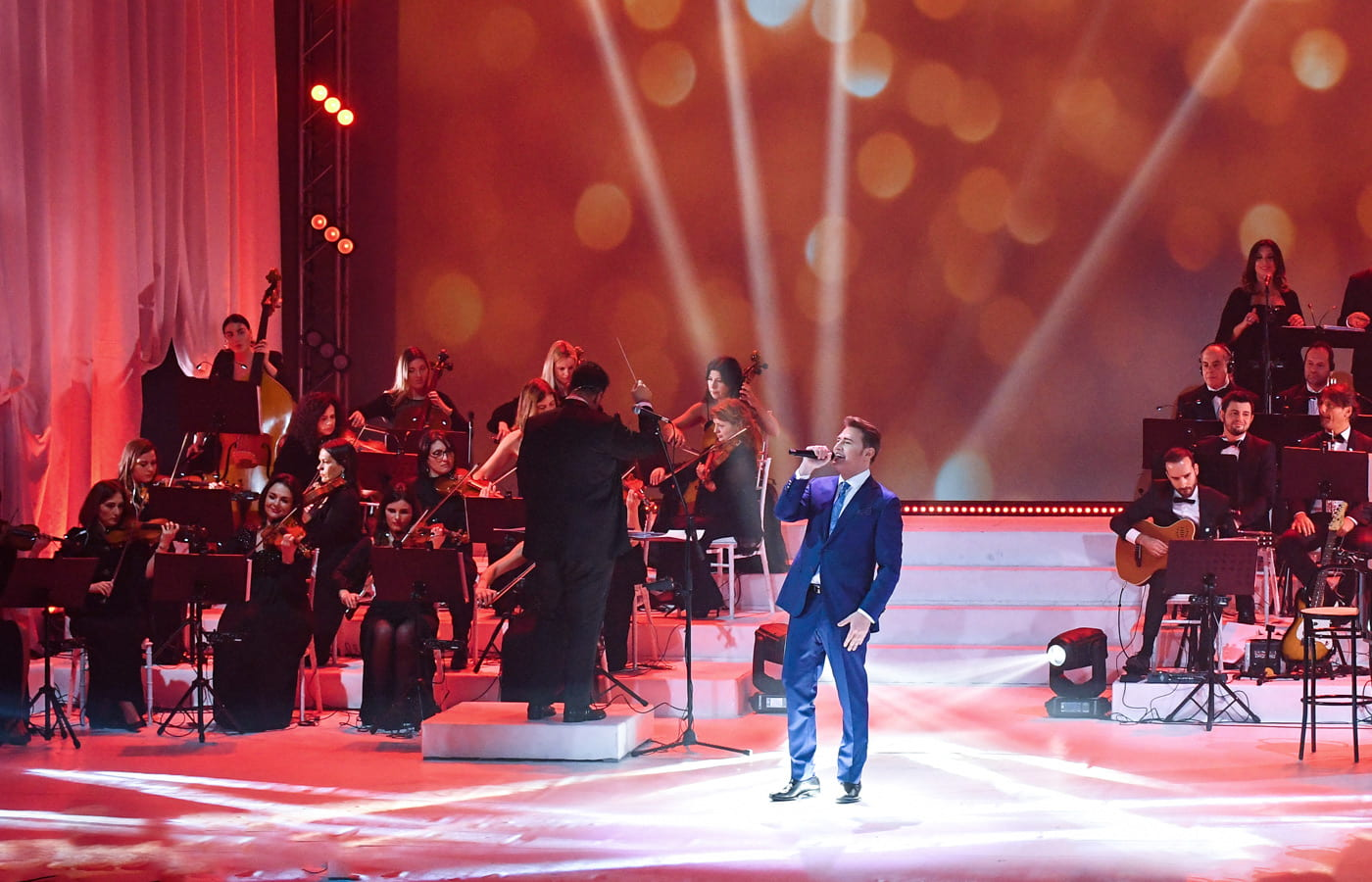 Pasquale Esposito singing on a glittering red stage.