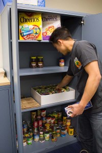 A volunteer stocks a Student Food Shelve at SJSU, where students with food insecurity can pick up canned and dry goods.