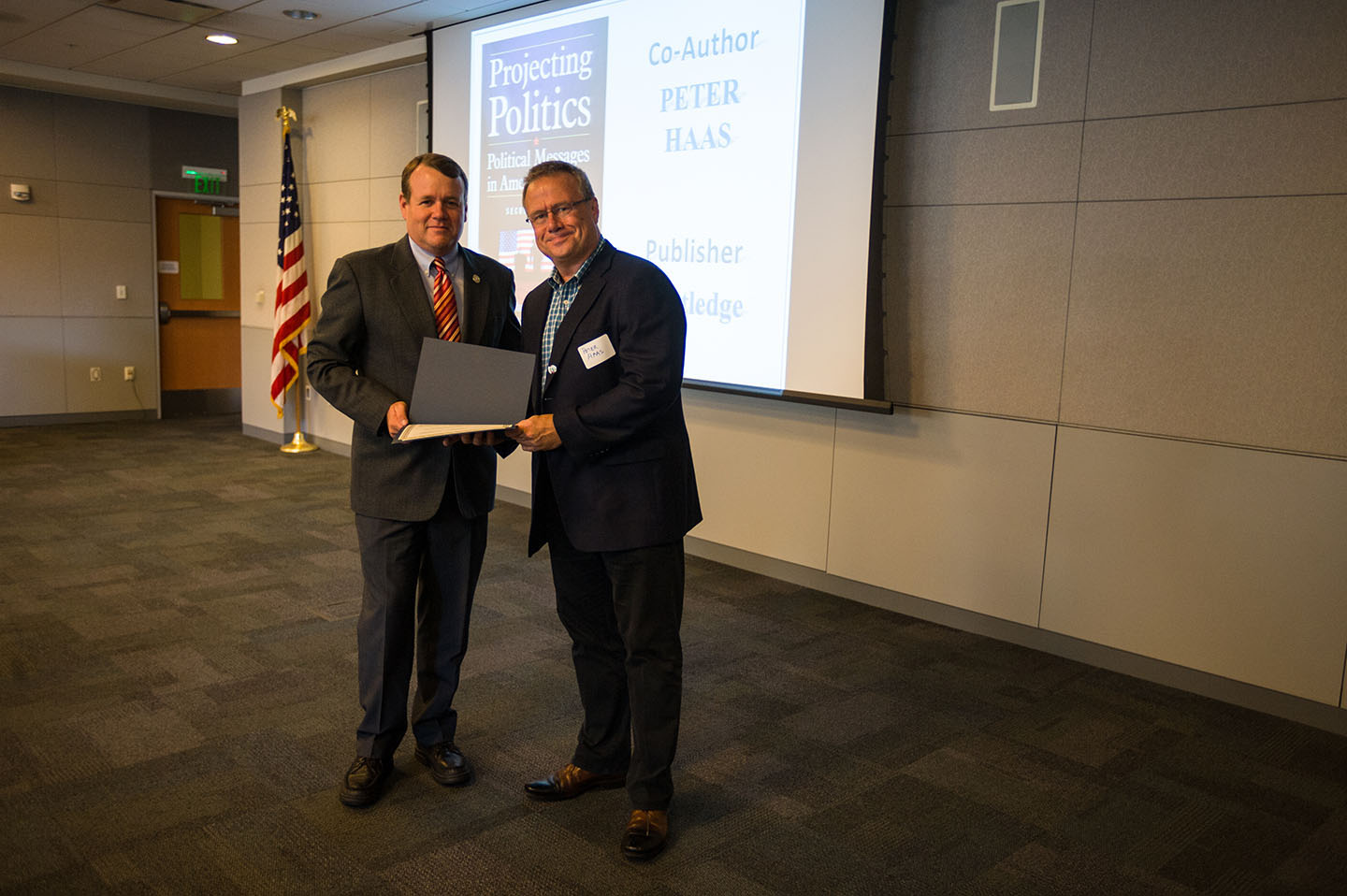 Provost Andy Feinstein, left, presents a certificate to Professor Peter Haas at the Annual Author Awards in October. Haas is one of two dozen faculty members honored at the event.