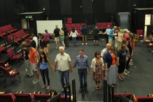 "Photo courtesy of Matthew Spangler Dr. Matthew Spangler, center right in gray, and Dr. David Kahn, center left in white, lead participants of a 2014 summer institute, ""The Immigrant Experience in California through Literature and Theatre"" through a performance exercise. The pair will host the program this summer with a National Endowment for the Humanities grant."
