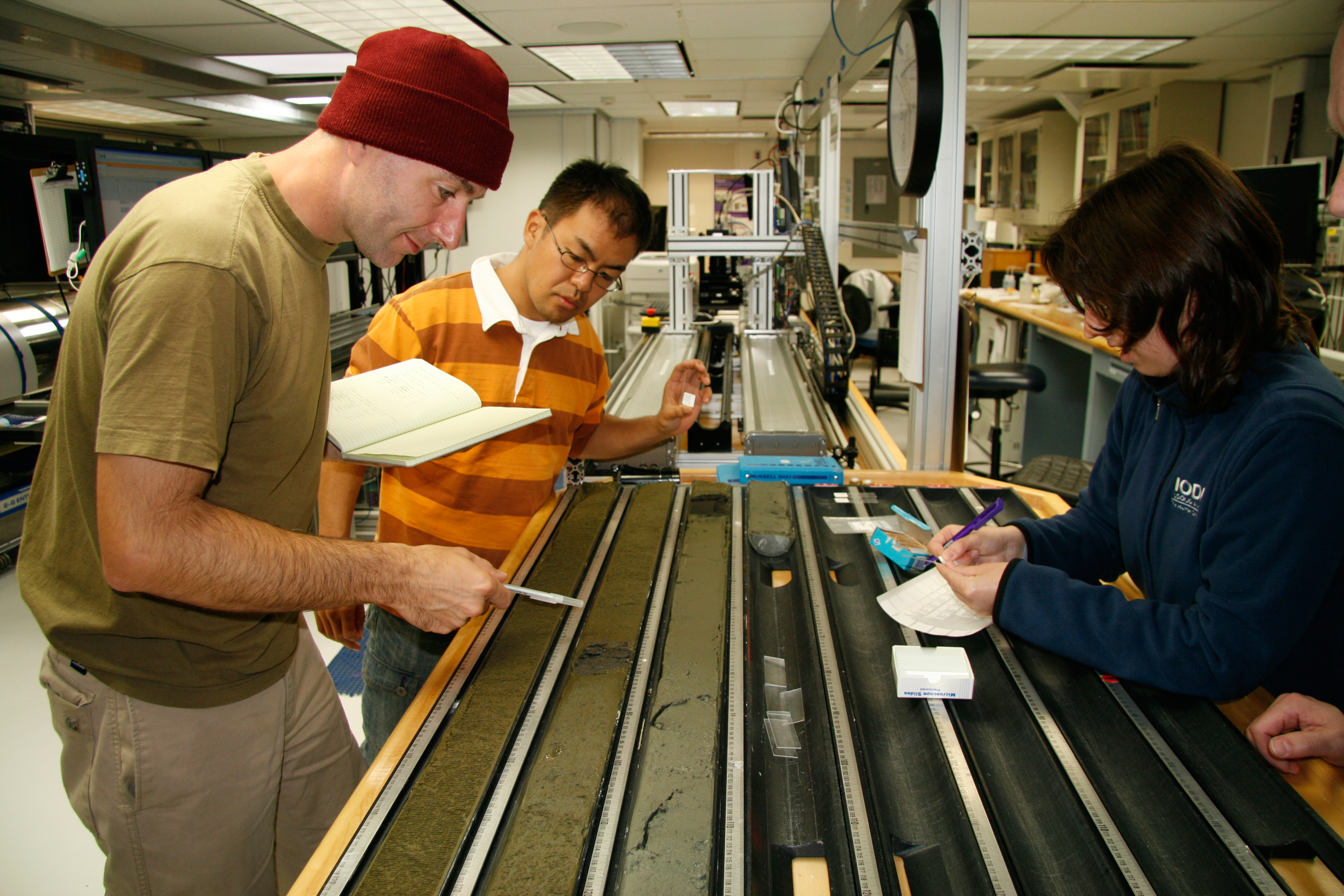 Dr. Ivano Aiello works with students on reviewing a sediment sample.