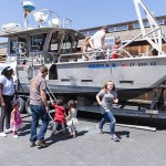 Children climb aboard a research boat.