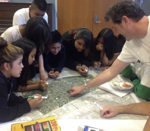 Using a map of the neighborhood, profesor Rick Kos leads youth through an exercise that helps them identify neighborhood assets and constraints. Photo by Dayana Salazar