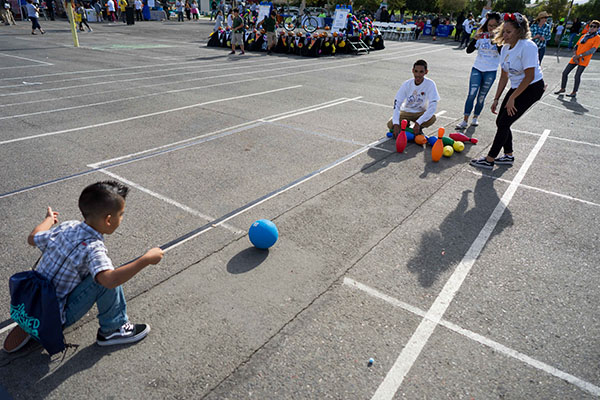 SJSU students lead children in a game of bowling. (Photo: James Tensuan, '15 Journalism)