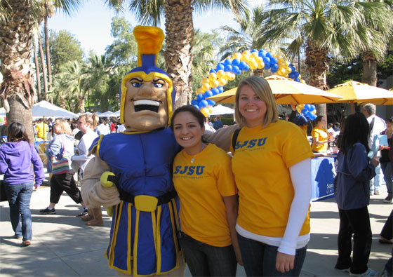 Two female students in gold SJSU shirt posing with Sammy Spartan.