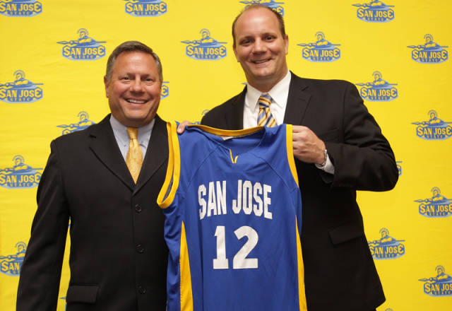 Two white men wearing suites, on left is Tim La Kose. Tim is holding up a SJSU basketball Jersey with the number 12 on it. They are standing infront of a yellow background with SJSU spartan logos.