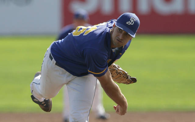 Blake McFarland, wearing a SJSU jersey and cap with white pants, after throwing the ball leaning over with one foot off the ground.
