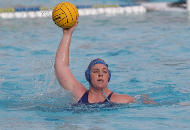 Allie Steward with arm raised yellow ball in hand ready to throw in the pool, wearing blue.