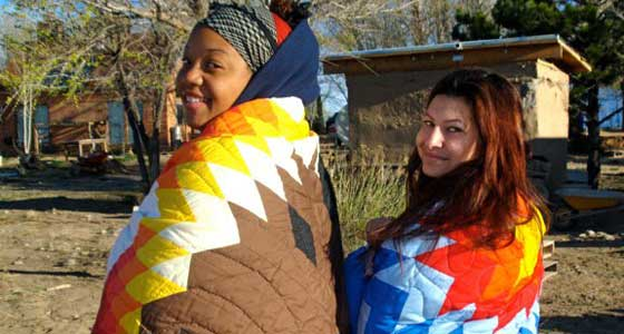 Two female students covered in colorful Navajo blankets.