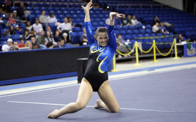 Katie Valleau, female gymnist, on the floor mats during routine. Finishes off routine with hands in the air.