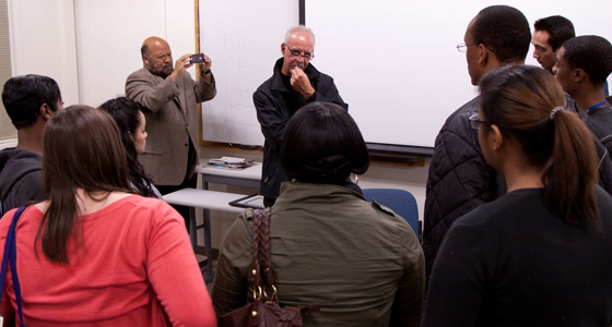 Students huddle around to talk with Los Angeles Times columnist Steve Lopez, as Bob Rucker, interim director of the School of Journalism and Mass Communications, takes a photo with his phone. Photo by Michelle Terris.