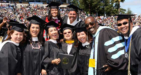A group of graduates pose with diplomas with a professor at commencement. All dressed in black cap and gowns smiling.