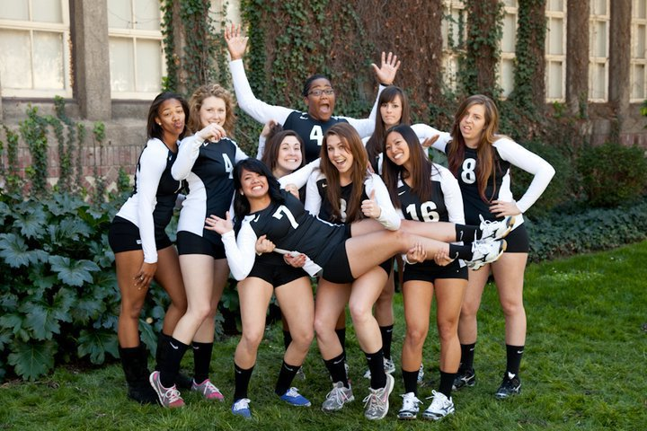 The volleyball team poses for a group photo wearing their uniforms.