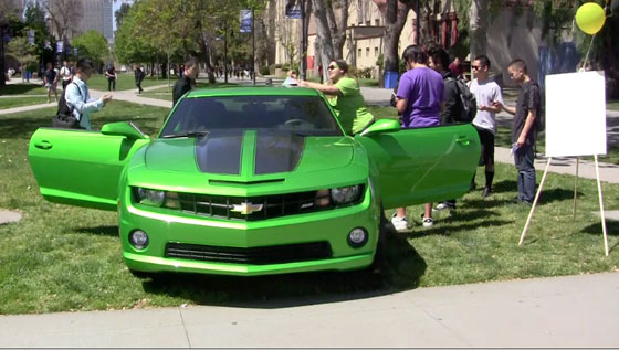 Students look at a green chevrolet car.