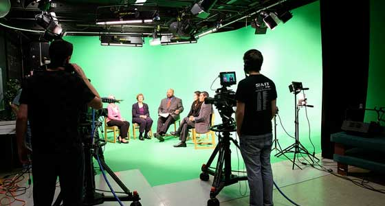 Students working in studio with camera. Guests are sitting in front of green screen.