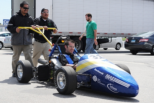 Two students push out a hybrid racecar, with a student inside, at the 2011 Formula Hybrid Competition in New Hampshire. Photo by Kathryn LoConte Lapierre.