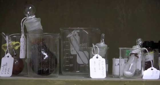 Glass beakers, tubes, tags red lightbulbs and other scientific tools.