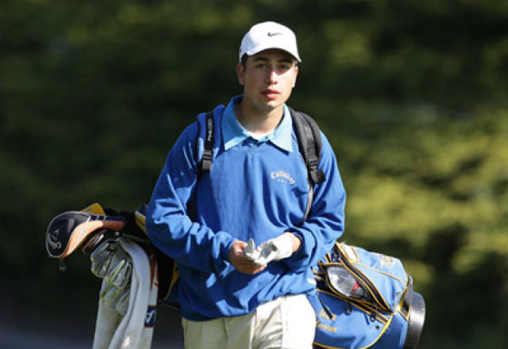Matt Hovan carrying golf equipment walking. Wearing Blue sweater, baseball cap, and tan pants.