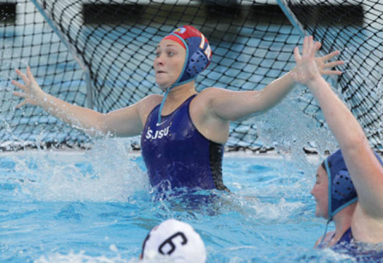 Lauren Lewis in the pool attempting to block the opposing team from scoring a goal, wearing a blue swimsuite.
