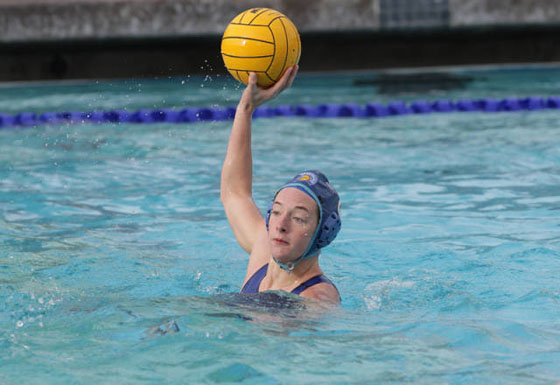 Kelly Stewart holds a waterpolo ball ready to throw.