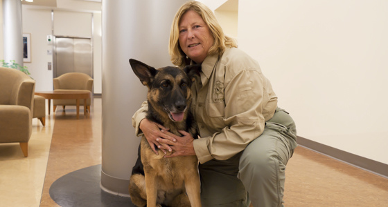 Woman posing with her K-9 canine partner.