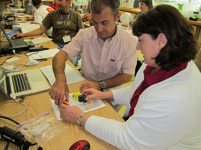 teachers working with models that will aid in computer designs