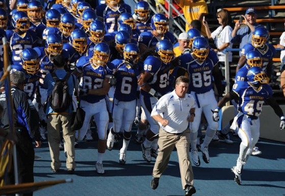 SJSU football team in uniform running out to the field with coach leading the way.