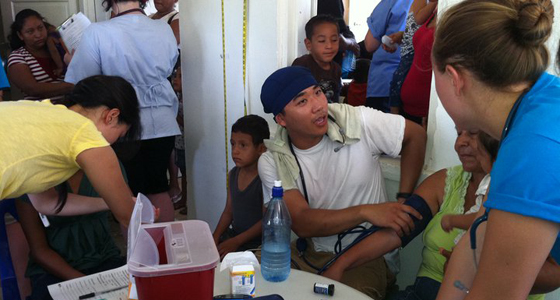 Nursing students work at a clinic in Belize to check people's blood pressure. Photo by Ruth Rosenblum.