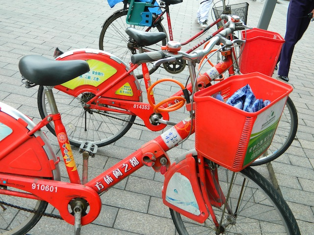A picture of a red bike share bicycle taken in China during a Global Technology Initiative trip. Bikes include a modular shape and contains a basket for carrying items.